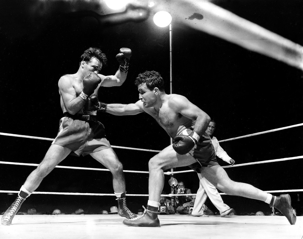 . FILE - This June 16, 1949, file photo, shows Jake LaMotta, right, fighting Marcel Cerdan in Briggs Stadium in Detroit, Mich. LaMotta knocked out Cerdan in the tenth round to become the new world middleweight champion. LaMotta, whose life was depicted in the film �Raging Bull,� died Tuesday, Sept. 19, 2017, at a Miami-area hospital from complications of pneumonia. He was 95. (AP Photo/File)