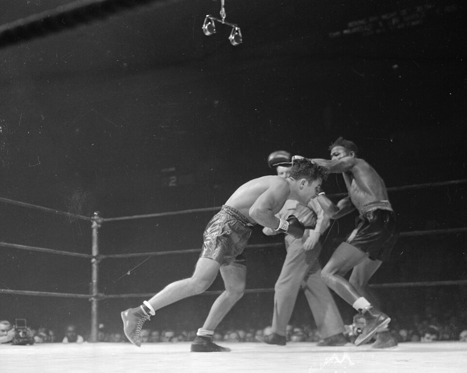. Jake LaMotta, left, Bronx middleweight, ducks a blow from Ray Robinson, the Harlem welterweight, in an early round of their ten-round bout in New York, Oct. 2, 1942.  Robinson won the decision to bring his all-winning string of victories to 125 in a row.  (AP Photo/Anthony Camerano)