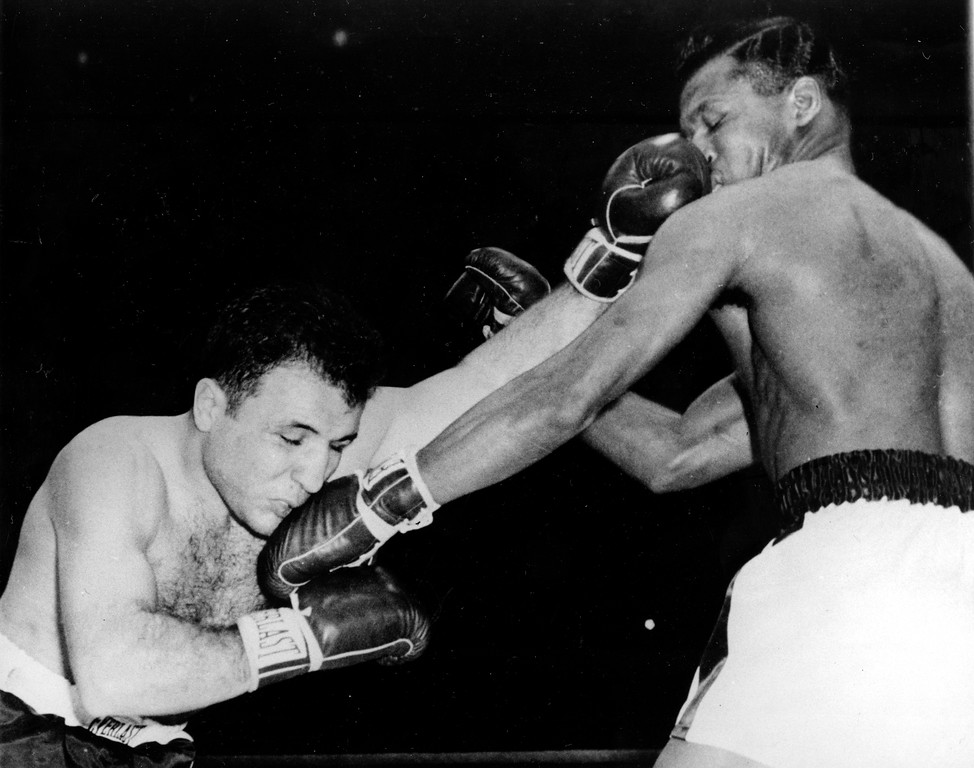 . Jake LaMotta, left, and challenger Sugar Ray Robinson exchange lefts to the face in first round of their middleweight championship bout at Chicago Stadium, Chicago, Ill., Feb. 14, 1951.  Robinson wrested the crown from LaMotta with a technical knockout in the 13th round.  (AP Photo)