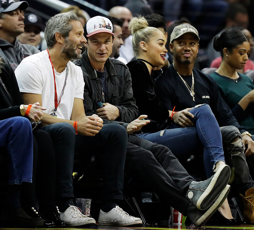 . Actor Jason Bateman, center left, and model Jasmine Sanders, center right, sit on the sideline for a NBA basketball game between the Atlanta Hawks and the Philadelphia 76ers in Atlanta, Saturday, Nov. 12, 2016. (AP Photo/David Goldman)