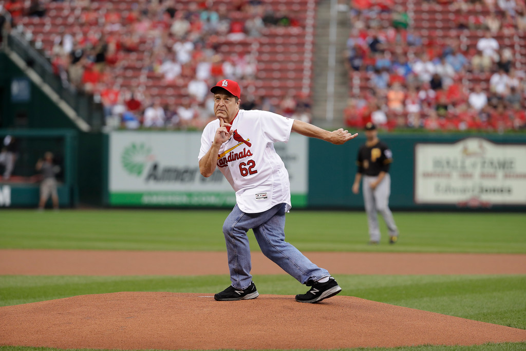 . Actor John Goodman clowns around before throwing out a first pitch before the start of a baseball game between the St. Louis Cardinals and the Pittsburgh Pirates Wednesday, July 6, 2016, in St. Louis. (AP Photo/Jeff Roberson)