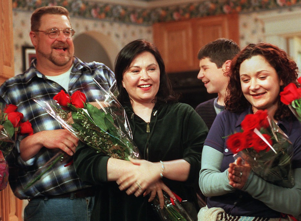 """. Comedienne/actress Roseanne, center, star of the longtime ABC sitcom \""""Roseanne,\"""" basks in applause with co-stars John Goodman, left, and Sara Gilbert after taping was completed on the 221st and final episode of the show, Friday, April 4, 1997, at Radford Studios in Los Angeles. Goodman plays Roseanne\'s husband on the show and Gilbert her daughter. (AP Photo/Chris Pizzello)"""