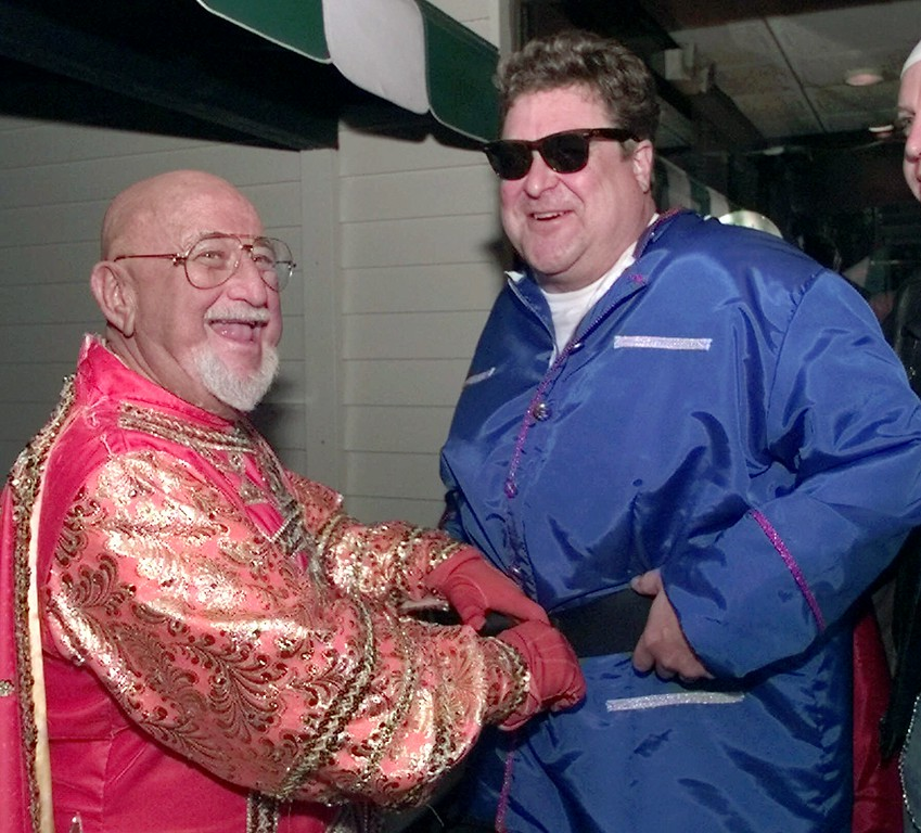 . New Orleans musician Pete Fountain, left, helps actor John Goodman adjust his costume at Commanders Palace in New Orleans Tuesday, Feb. 16, 1999. Fountain was preparing to lead his Half Fast Marching Club through the streets of New Orleans starting the Mardi Gras celebration and Goodman was joining the annual march. (AP Photo/Bill Haber)