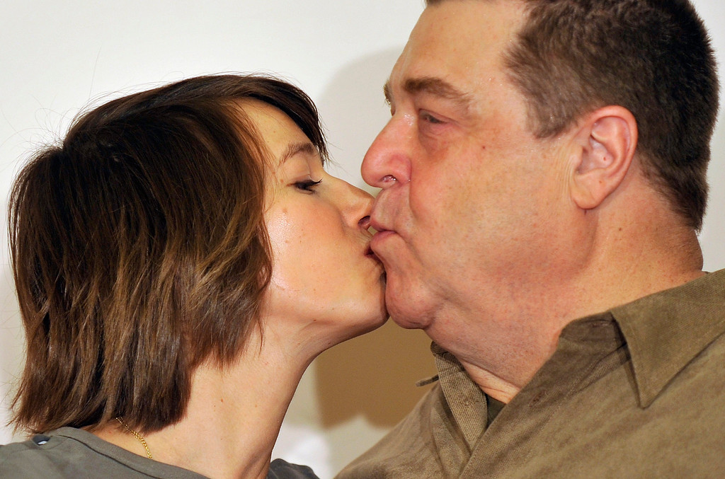 """. Actress Johanna Wokalek, left, and actor John Goodman, right, kisses each other during a photo call for the movie \""""Die Paepstin\"""" in Berlin, Monday, Oct. 19, 2009. (AP Photo/Gero Breloer)"""