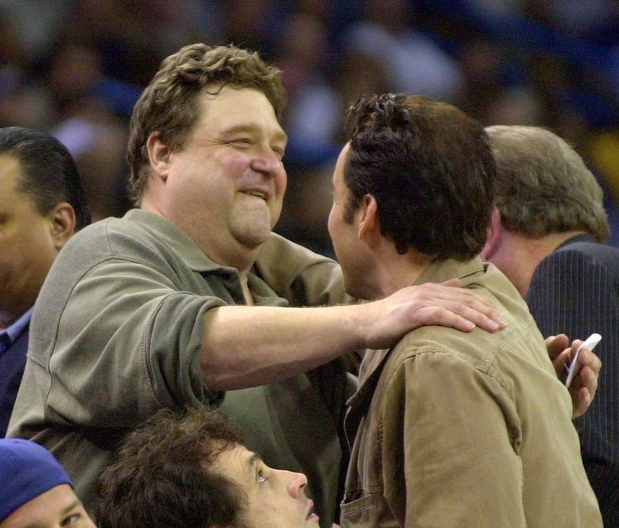 . Actor John Goodman greets John Cusack, right, at courtside of the New Orleans Hornets-Philadelphia 76ers game in New Orleans Tuesday, Nov. 19, 2002.  (AP Photo/Bill Haber)