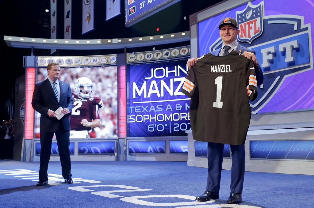 . Texas A&M quarterback Johnny Manziel poses for photos after being selected by the Cleveland Browns as the 22nd pick in the first round of the 2014 NFL Draft, Thursday, May 8, 2014, in New York. (AP Photo/Craig Ruttle)