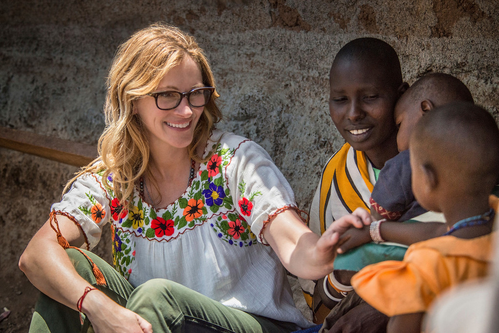 ". In this image released by NBC, actress Julia Roberts, left, interacts with a child while filming a special edition of the survival series ""Running Wild with Bear Grylls,\"" in Kenya called, \""Running Wild with Bear Grylls for Red Nose Day,\"" airing on May 25. (Mia Collis/NBCUniversal via AP)"