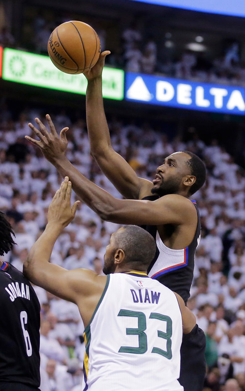 . Los Angeles Clippers forward Luc Richard Mbah a Moute shoots as Utah Jazz center Boris Diaw (33) defends during the first half in Game 6 of an NBA basketball first-round playoff series Friday, April 28, 2017, in Salt Lake City. (AP Photo/Rick Bowmer)