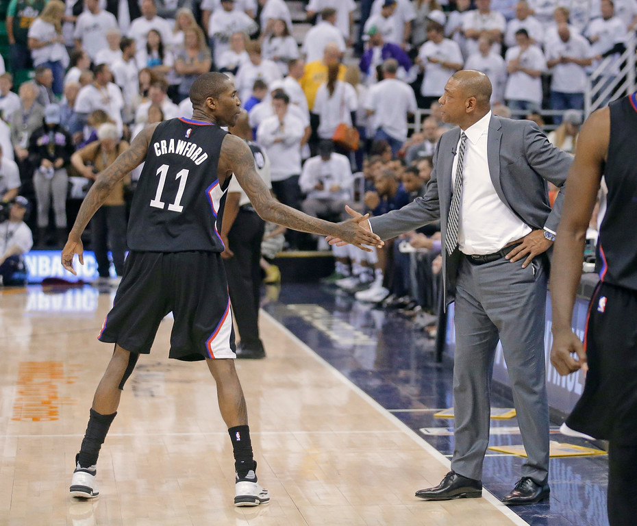 . Los Angeles Clippers guard Jamal Crawford (11) receives congratulations from Clippers coach Doc Rivers near the end of Game 6 of the team\'s NBA basketball first-round playoff series against the Utah Jazz on Friday, April 28, 2017, in Salt Lake City. The Clippers won 98-93, tying the series. (AP Photo/Rick Bowmer)