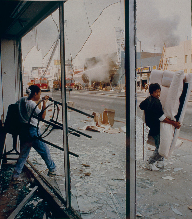 . Looters on Vermont Avenue steal items from a furniture store while the fire department responds to a building that had been torched by vandals. April 30, 1992. (Photo by John McCoy/Los Angeles Daily News)