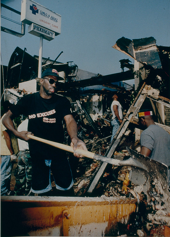 . Los Angeles Clipper cener Olden Polynice used his 250 pound 7 foot tall fram to assist in cleanup efforts after the Los Angeles Riots. Here he is seen shoveling debris into a dumpster at the site of a business that was burned to the ground near the Los Angeles Sports Arena. May 5, 1992. photo by John McCoy/Los Angeles Daily News)