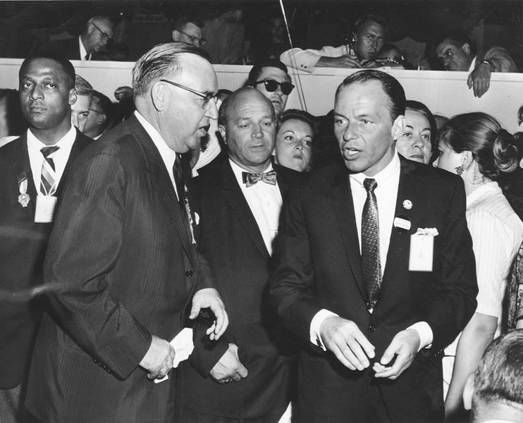 """. Frank Sinatra talks to Gov. Edmund G. (Pat) Brown on the floor of the convention hall at the Sports Arena. Note Frankie\'s \""""Stop Khrushchev\"""" button. Photograph dated July 13, 1960.  (Photo courtesy Los Angeles Public Library)"""