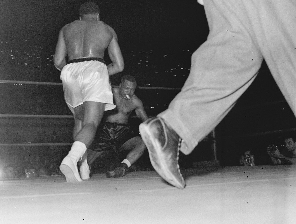 . Archie Moore is shown being knocked down, losing his mouthpiece in the process, for the first of three times in the fourth round by young Cassius Clay of Louisville, KY, in the Los Angeles Sports Arena, November 15, 1962.  When Moore went down for the third time, referee Tommy Hart stopped the fight and awarded Clay the victory without bothering to count.  (AP Photo)