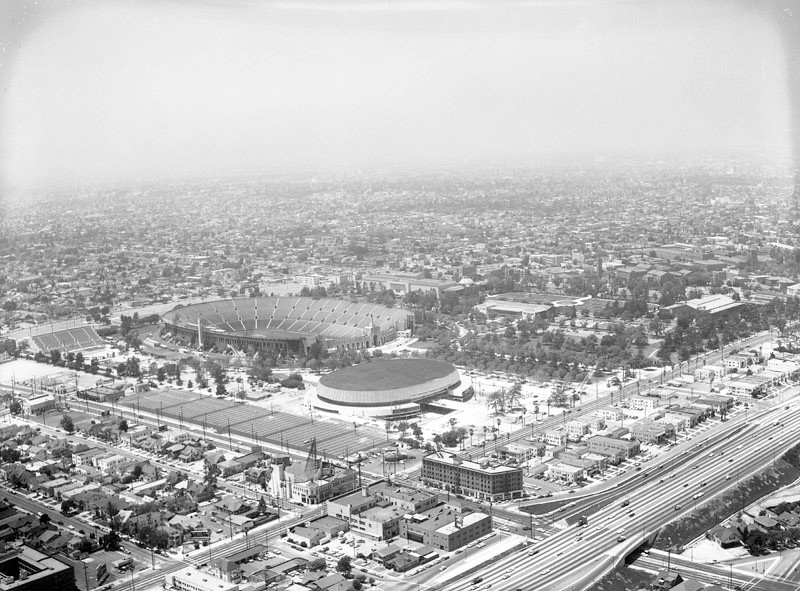 . Aerial view shows two major centers of interest, the Memorial Coliseum (left) and the Memorial Sports Arena (center); view is looking northwest. The Los Angeles Memorial Coliseum, located at 3911 S. Figueroa Street, was officially opened on May 1, 1923. The Los Angeles Memorial Sports Arena, located at 3939 S. Figueroa Street, was officially opened on July 4, 1959. Figueroa Street can be seen from bottom left corner to middle right; the Harbor (110) Freeway runs across bottom right corner; Martin Luther King Jr. Boulevard is seen from middle left to bottom right corner. Photograph taken for Pioneer Flint Kote. Photograph dated June 12, 1959.  (Photo courtesy Los Angeles Public Library)