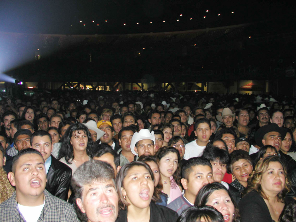 """. Fans sing along with musical group \""""Los Tigres Del Norteat\"""" at the O.L.A.W. (Organization of Los Angeles Workers) benefit concert for Immigrant Legalization at the Los Angeles Sports Arena March 23, 2002 in Los Angeles, CA.  (Photo by Alexander Sibaja/Getty Images)"""