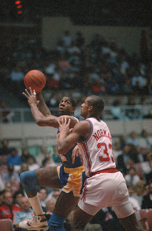 ". Los Angeles Lakers\' Earvin ""Magic\"" Johnson (left) goes to the basket over Los Angeles Clippers Ken Norman during first quarter NBA Action at the Sports Arena in Los Angeles, Tuesday evening, Jan. 30, 1990. Johnson returned to the court after missing Monday\'s game due to the flu. (AP Photo/Reed Saxon)"
