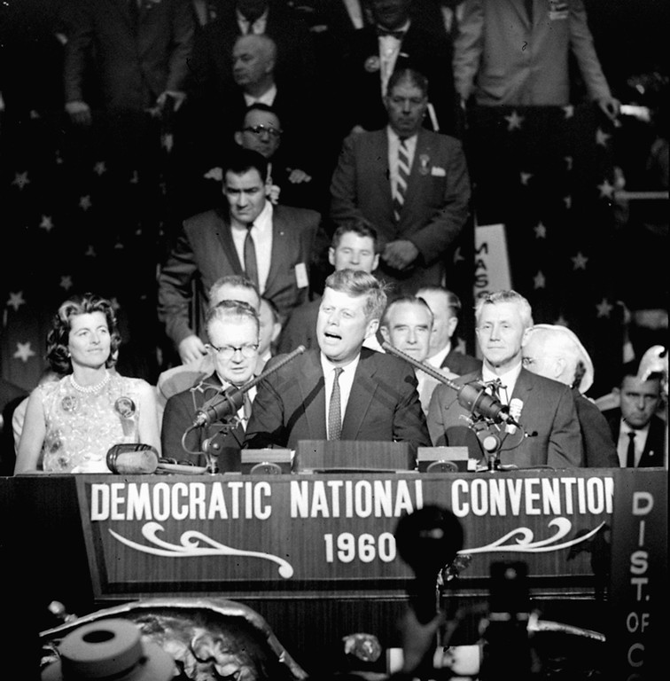 """. Sen. John F. Kennedy tells Democratic convention delegates, \""""we will carry the fight to the people in the fall and we shall win,\"""" during a brief appearance on the rostrum of the Los Angeles Sports Arena where he was nominated as the party\'s presidential candidate, July 14, 1960.  Standing beside him are his sister, Mrs. Peter Lawford, and Leonard Reinsch, convention director.  (AP Photo)"""