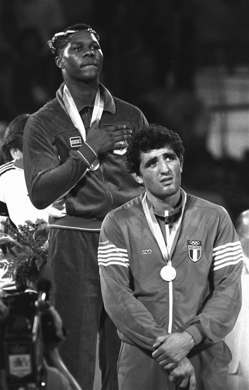 . Tyrell Biggs of Philadelphia, Pa., proudly listens to the National Anthem Saturday, August 11, 1984,  after he was given the gold medal during awards ceremonies at the Los Angeles Sports Arena for his 4-1 super heavyweight decision over Francesco Damiani of Italy, right, in the Olympic boxing event.  (AP Photo/Michel Lipchitz)