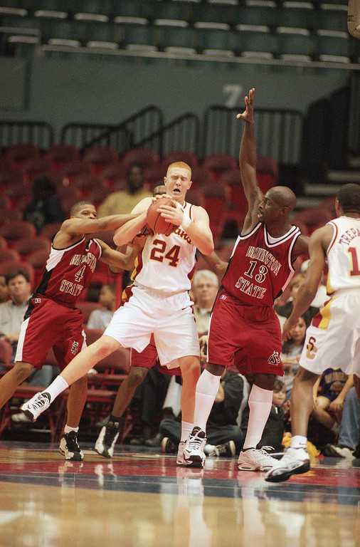 . Brian Scalabrine (24) of Southern California hauls in a rebound between Washington State guard Jan-Michael Thomas (4) and forward Kojo Mensah-Bonsu (13) in the first half of their Pac-10 game on Saturday, Feb. 27, 1999 at the Los Angeles Sports Arena.  (AP Photo/Kevin Karzin)