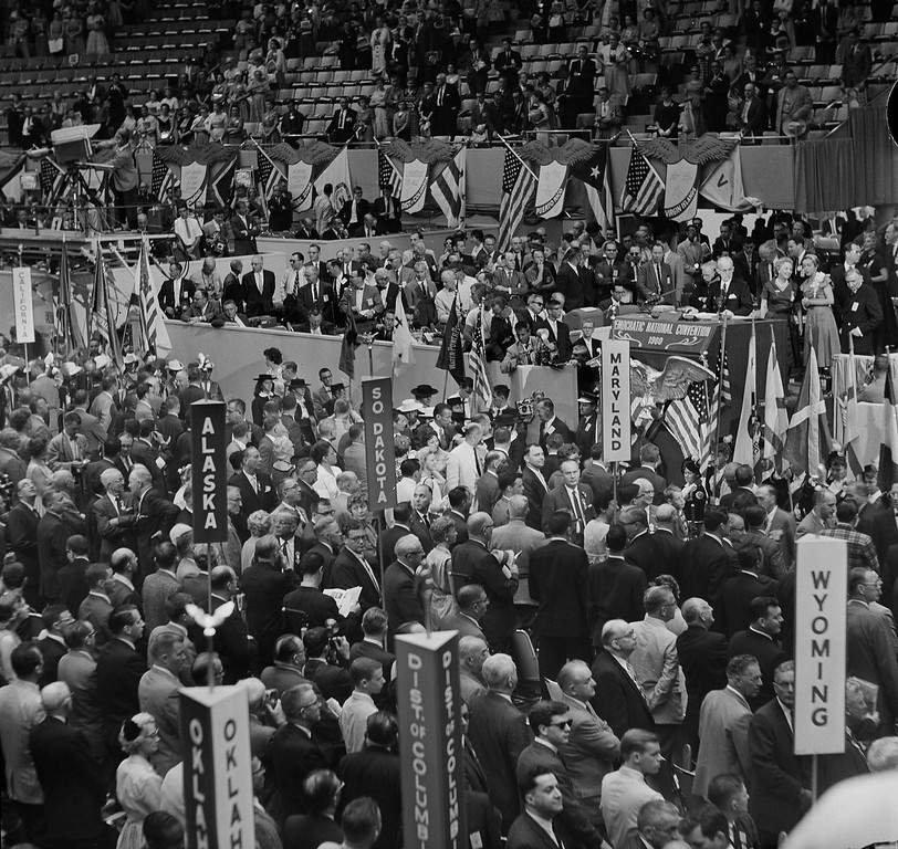 . This is a general view of the rostrum area as the Democratic National Convention began in Los Angeles\' Sports Arena on July 11, 1960. Chairman Paul Butler of the Democratic national committee is at the podium at right as color guard marches into the arena.  (AP Photo)
