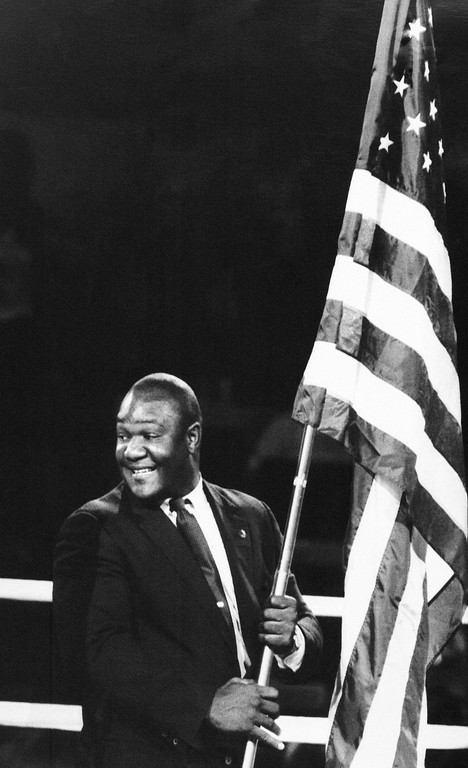 . George Foreman, 1968 gold medalist and former heavyweight champion, carries the American flag in the opening of the Olympic boxing preliminaries at the Los Angeles Memorial Sports Arena, July 30, 1984. (AP Photo/Lenny Ignelzi)