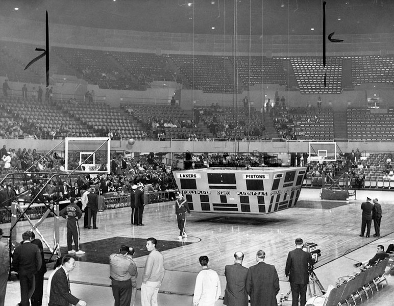 . Pair of Detroit basketballers engage in pre-game drill while Sports Arena officials ponder ridding court of 5400 pound scoreboard that fell to the floor shortly before the scheduled start of the Lakers-Pistons game. Workmen eventually pulled the scoreboard from the floor on dollies and Los Angeles proceeded to down Detroit, 107-100, before 2978 fans. Photo dated: February 28, 1962. (Photo courtesy Los Angeles Public Library)