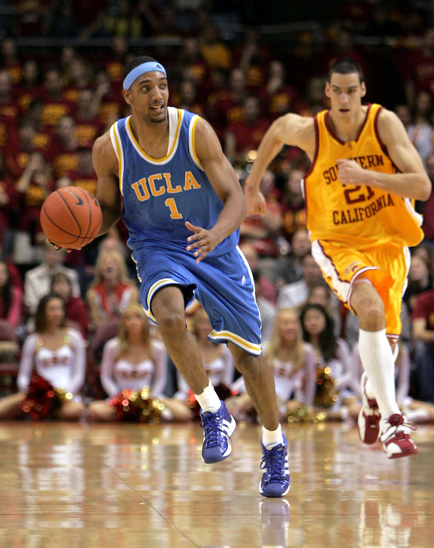 . LOS ANGELES - JANUARY 29:  Dijon Thompson #1 ofthe UCLA Bruins carries the ball as Rory O\'Neil #21 of the USC Trojans pursues on January 29, 2005 at the Los Angeles Sports Arena in Los Angeles, California. UCLA won the game 72-69.  (Photo by Stephen Dunn/Getty Images)