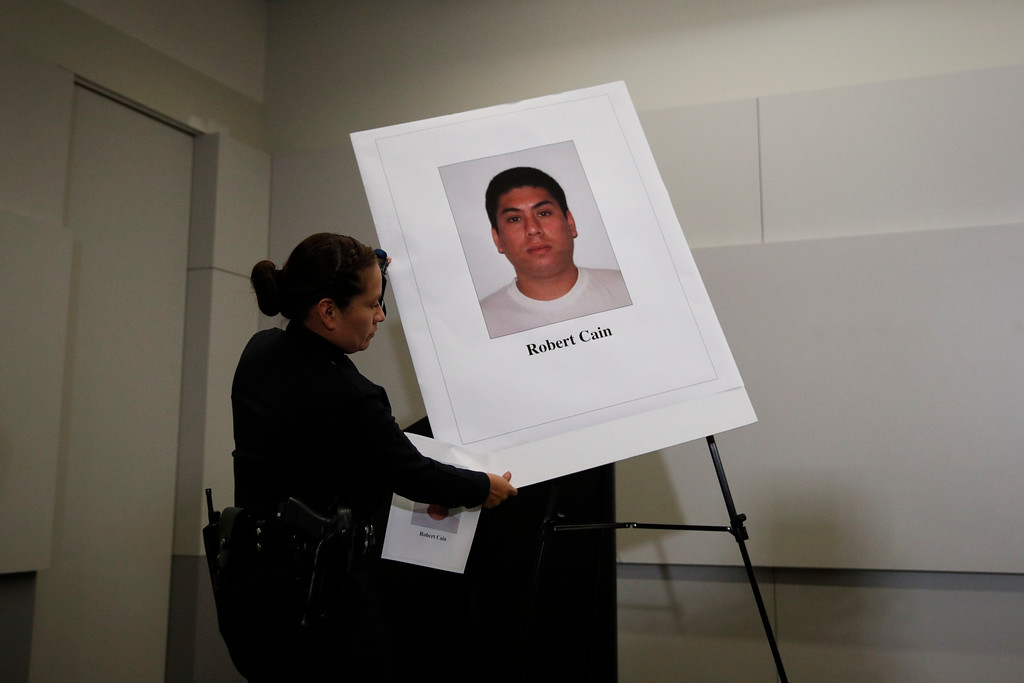 . Los Angeles police officer Liliana Preciado sets up a display board showing an images of officer Robert Cain in preparation for a news conference Thursday, June 22, 2017, in Los Angeles. Cain has been arrested for allegedly having sex with a 15-year-old cadet who\'s suspected of joyriding in stolen patrol cars. (AP Photo/Jae C. Hong)