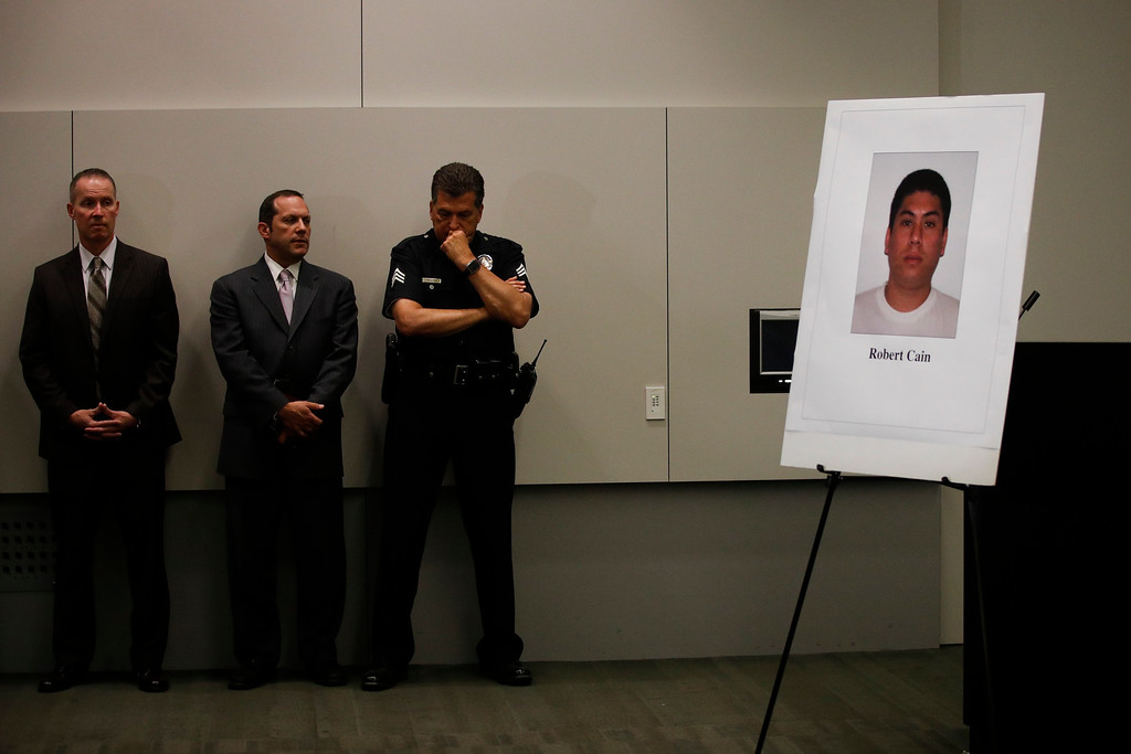 . Los Angeles police officials stand near a display board showing an image of officer Robert Cain as they listen to Police Chief Charlie Beck during a news conference Thursday, June 22, 2017, in Los Angeles. Cain has been arrested for allegedly having sex with a 15-year-old cadet who\'s suspected of joyriding in stolen patrol cars. (AP Photo/Jae C. Hong)