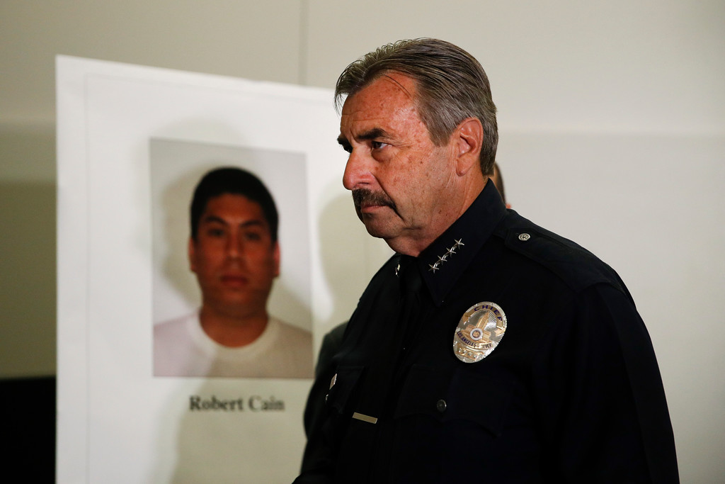 . Los Angeles Police Chief Charlie Beck walks past a display board showing an image of officer Robert Cain after a news conference Thursday, June 22, 2017, in Los Angeles. Cain has been arrested for allegedly having sex with a 15-year-old cadet who\'s suspected of joyriding in stolen patrol cars. (AP Photo/Jae C. Hong)