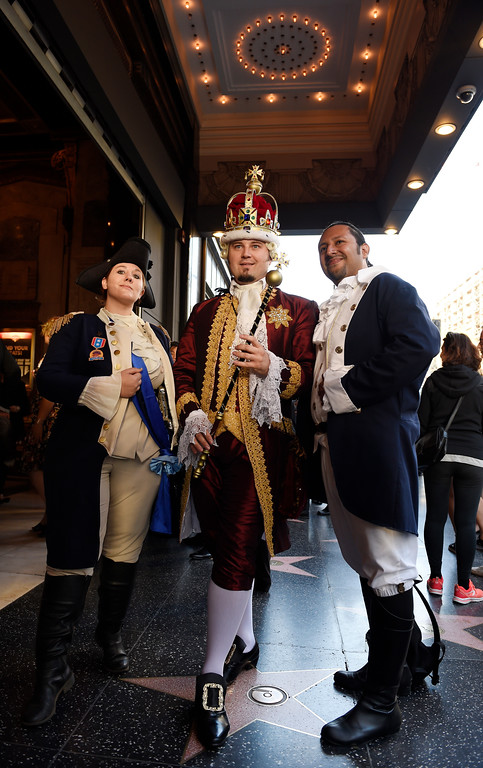 ". Katie Aiani, left, Chad Evett, center, and Miguel Godinez pose for photographers in Colonial Era costumes on the opening night of the Los Angeles run of ""Hamilton: An American Musical\"" at the Pantages Theatre Wednesday, Aug. 16, 2017, in Los Angeles. (Photo by Chris Pizzello/Invision/AP)"