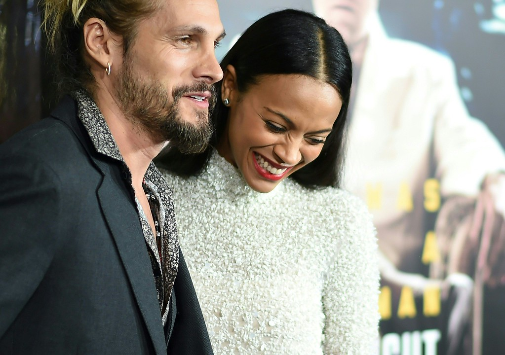 ". Artist Marco Perego and actress Zoe Saldana arrive for the  for the world premiere of Warner Bros. ""Live By Night,\"" January 9, 2017 at the TCL Chinese Theater in Hollywood, California. / AFP / Robyn Beck        (Photo credit should read ROBYN BECK/AFP/Getty Images)"