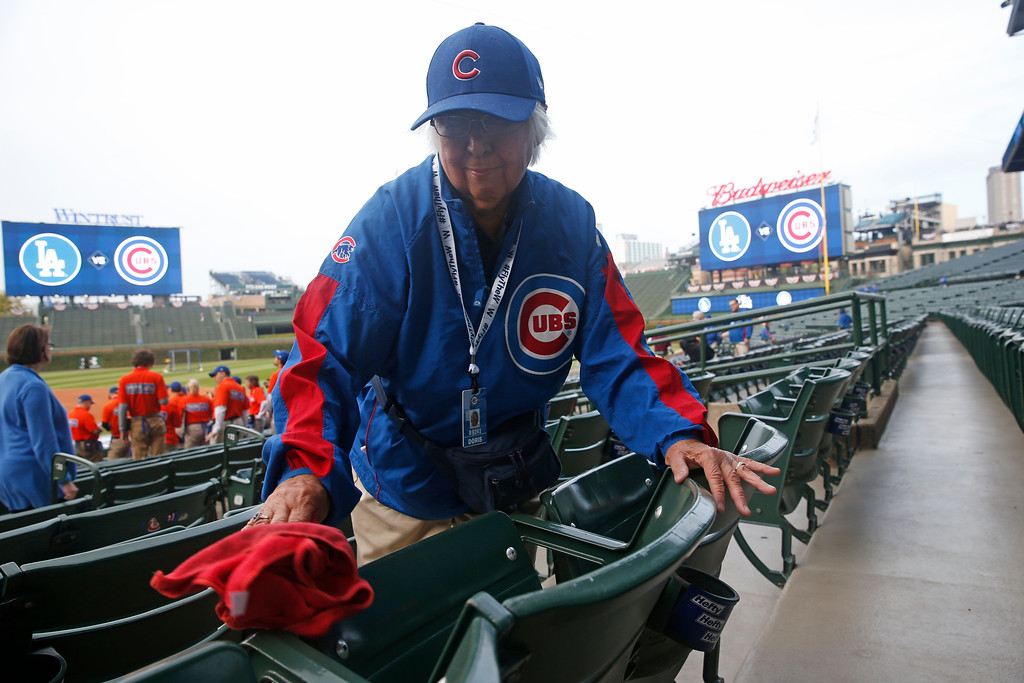 . Doris Hathy wipes down seats at Wrigley Field before fans arrive for Game 1 of baseball\'s National League Championship Series between the Chicago Cubs and the Los Angeles Dodgers, Saturday, Oct. 15, 2016, in Chicago. (AP Photo/Nam Y. Huh)