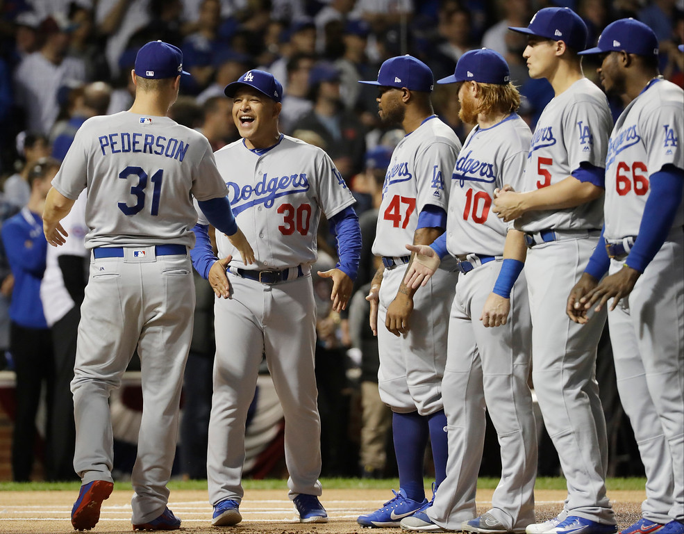 . Los Angeles Dodgers manager Dave Roberts (30) laughs with Los Angeles Dodgers\' Joc Pederson (31) as the team is introduced before Game 1 of the National League baseball championship series against the Chicago Cubs Saturday, Oct. 15, 2016, in Chicago. (AP Photo/David J. Phillip)