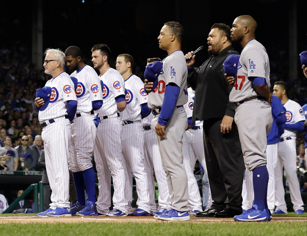 . Chicago Cubs and Los Angeles Dodgers players observes the national anthem before Game 1 of the National League baseball championship series Saturday, Oct. 15, 2016, in Chicago. (AP Photo/David J. Phillip)