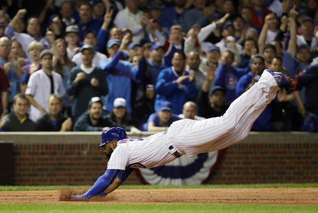 . Chicago Cubs right fielder Jason Heyward (22) dives to third base for a triple during the second inning of Game 1 of the National League baseball championship series against the Los Angeles Dodgers Saturday, Oct. 15, 2016, in Chicago. (AP Photo/David J. Phillip)