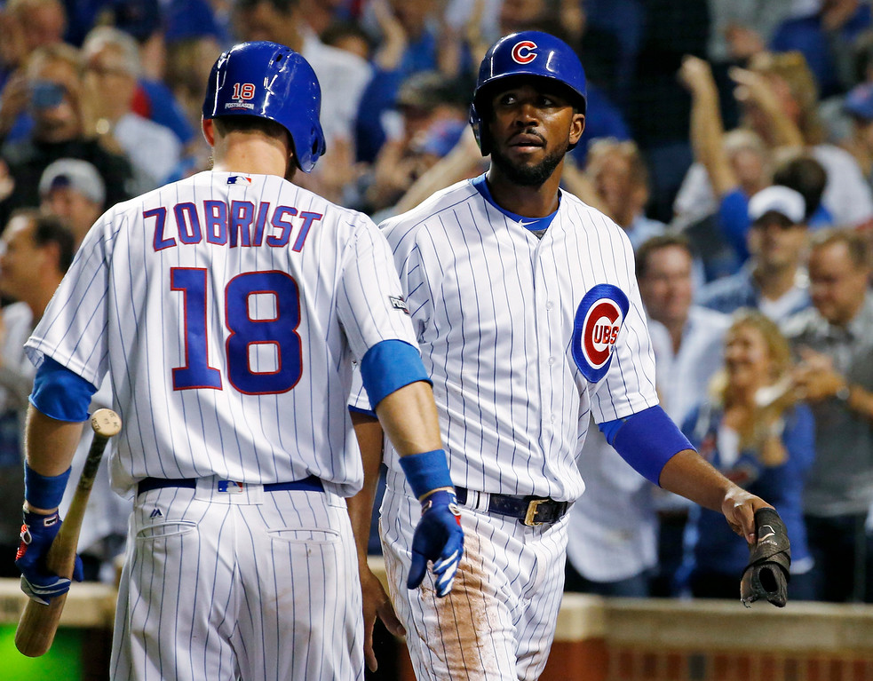 . Chicago Cubs\' Dexter Fowler, right, celebrates with Ben Zobrist after scoring a run during the first inning of Game 1 of the National League baseball championship series against the Los Angeles Dodgers Saturday, Oct. 15, 2016, in Chicago. (AP Photo/Nam Y. Huh)