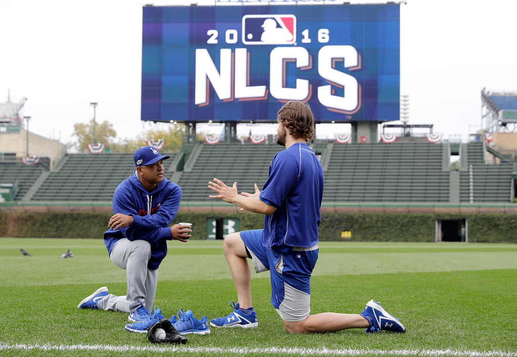 . Los Angeles Dodgers manager Dave Roberts, left,  talks to Clayton Kershaw as players warm up before Game 1 of baseball\'s National League Championship Series against the Chicago Cubs, Saturday, Oct. 15, 2016, in Chicago. (AP Photo/Morry Gash)