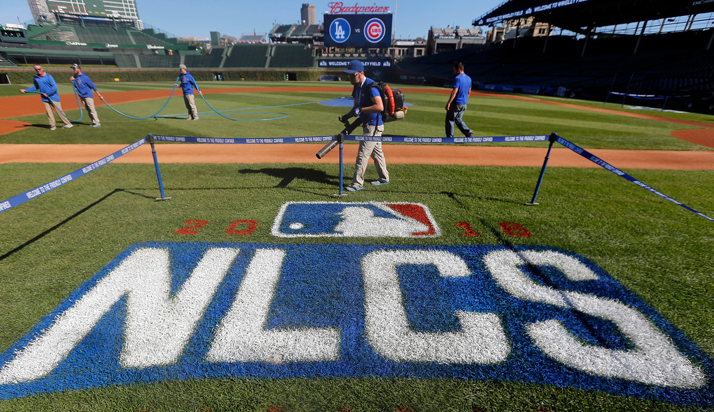 . A grounds crew prepare the field for baseball\'s National League Championship Series at Wrigley Field, Friday, Oct. 14, 2016, in Chicago. The Chicago Cubs host Game 1 of the series against the Los Angeles Dodgers on Saturday. (AP Photo/Charles Rex Arbogast)
