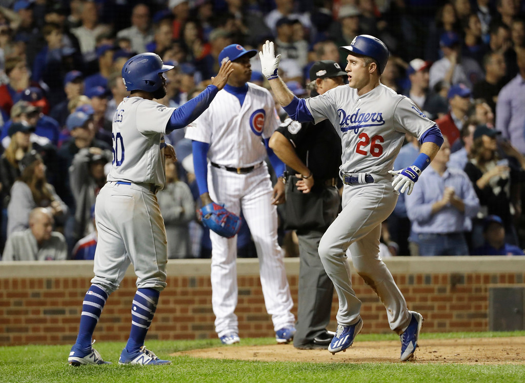 . Los Angeles Dodgers\' Chase Utley (26) celebrates with Andrew Toles (60) after scoring during the eighth inning of Game 1 of the National League baseball championship series against the Chicago Cubs Saturday, Oct. 15, 2016, in Chicago. (AP Photo/David J. Phillip)