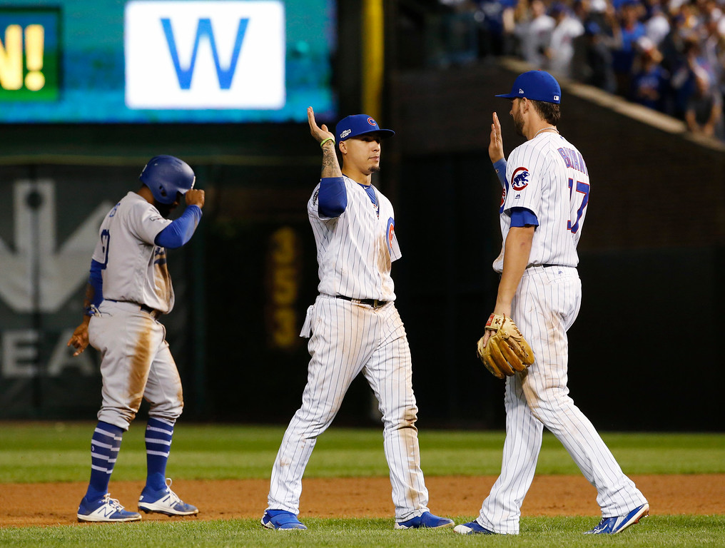 . Chicago Cubs second baseman Javier Baez, left, and third baseman Kris Bryant (17) celebrate after Game 1 of the National League baseball championship series against the Los Angeles Dodgers Saturday, Oct. 15, 2016, in Chicago. The Cubs won 8-4 to take a 1-0 lead in the series. (AP Photo/Nam Y. Huh)