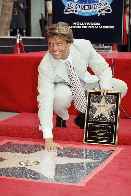 . Latin pop singer Luis Miguel poses with his new star on the Hollywood Walk of Fame on Thursday, Sept. 26, 1996 in the Hollywood section of Los Angeles. The 26-year-old singer, who has sold over 25 million albums worldwide, was awarded with the 2,073rd star on the Walk of Fame. (AP Photo/Chris Pizzello)