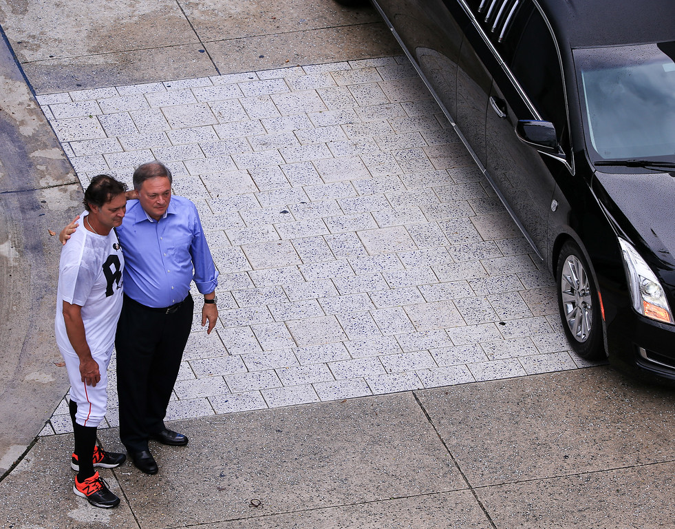 . MIAMI, FL - SEPTEMBER 28: Miami Marlins owner Jeffrey Loria, right, and manager Don Mattingly, left, look on as Miami Marlins players and members of the Marlins organization and their fans surround the hearse carrying Miami Marlins pitcher Jose Fernandez to pay their respects on September 28, 2016 in Miami, Florida. Mr. Fernandez was killed in a weekend boat crash in Miami Beach along with two friends. (Photo by Rob Foldy/Getty Images)