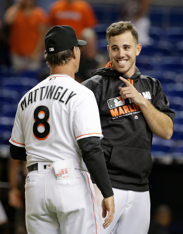 . Miami Marlins starting pitcher Jose Fernandez, right, celebrates with manager Don Mattingly (8) after the Marlins defeated the Pittsburgh Pirates 3-1 in a baseball game, Tuesday, May 31, 2016, in Miami. Fernandez pitched seven scoreless innings. (AP Photo/Wilfredo Lee)