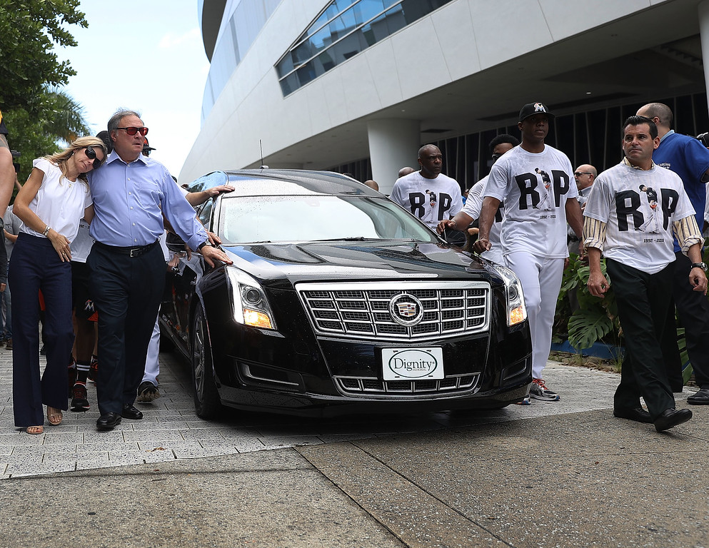 . MIAMI, FL - SEPTEMBER 28:  Miami Marlins owner,  Jeffrey Loria (2nd L) and his wife Julie Loria along with players and other members of the Marlins organization and their fans walk next to the hearse carrying Miami Marlins pitcher Jose Fernandez as they  pay their respects as they pass in front of the Marlins baseball stadium on September 28, 2016 in Miami, Florida.  Mr. Fernandez was killed in a weekend boat crash in Miami Beach along with two friends.  (Photo by Joe Raedle/Getty Images)