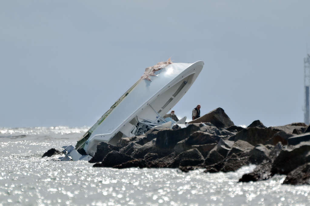 """. File - Investigators look at a boat overturned on a jetty, Sunday, Sept. 25, 2016, off Miami Beach, Fla. Miami Marlins pitcher Jose Fernandez was the \""""probable\"""" operator of the speeding boat that crashed into a Miami Beach jetty on Sept. 25, 2016, killing the baseball star and two other men, according to a report issued Thursday, March 16, 2017, by the Florida Fish and Wildlife Conservation Commission, which investigated the accident. (AP Photo/Gaston De Cardenas)"""