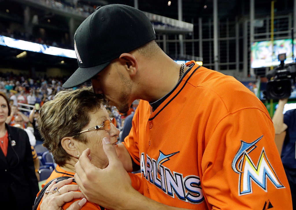. Miami Marlins starting pitcher Jose Fernandez, right, kisses his grandmother Olga Fernandez, of Cuba, left, following the Marlins\' 10-1 victory over the Colorado Rockies during an opening day baseball game, Monday, March 31, 2014, in Miami. (AP Photo/Lynne Sladky)