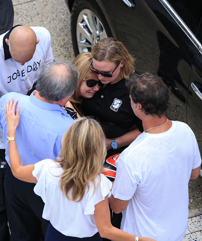 . MIAMI, FL - SEPTEMBER 28: Miami Marlins owner Jeffrey Loria, left, and manager Don Mattingly, right, consult the late Jose Fernandez\' mother Maritza Fernandez as Miami Marlins players and members of the Marlins organization and their fans surround the hearse carrying Miami Marlins pitcher Jose Fernandez to pay their respects on September 28, 2016 in Miami, Florida. Mr. Fernandez was killed in a weekend boat crash in Miami Beach along with two friends. (Photo by Rob Foldy/Getty Images)