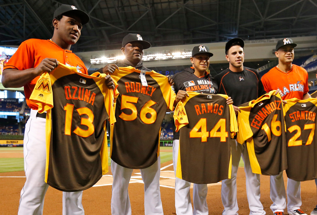 . Miami Marlins pose for photos after receiving their All-Star Game jerseys during a ceremony on the field before the start of a baseball game against the Cincinnati Reds, Sunday, July 10, 2016, in Miami. From left, Marcell Ozuna (13), Fernando Rodney (56), A.J. Ramos (44), Jose Fernandez (16) and Giancarlo Stanton (27). (AP Photo/Wilfredo Lee)