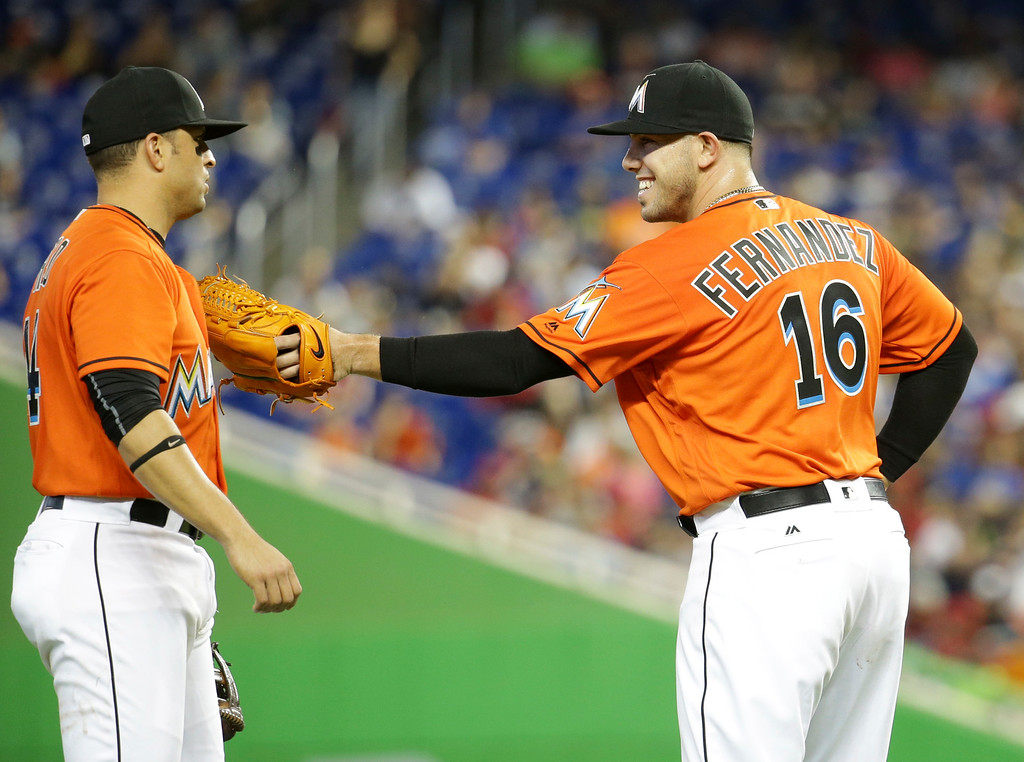 . Miami Marlins starting pitcher Jose Fernandez (16) laughs with third baseman Martin Prado after striking out the New York Mets\' first batter, Alejandro De Aza, during the first inning of a baseball game, Sunday, June 5, 2016, in Miami. (AP Photo/Lynne Sladky)